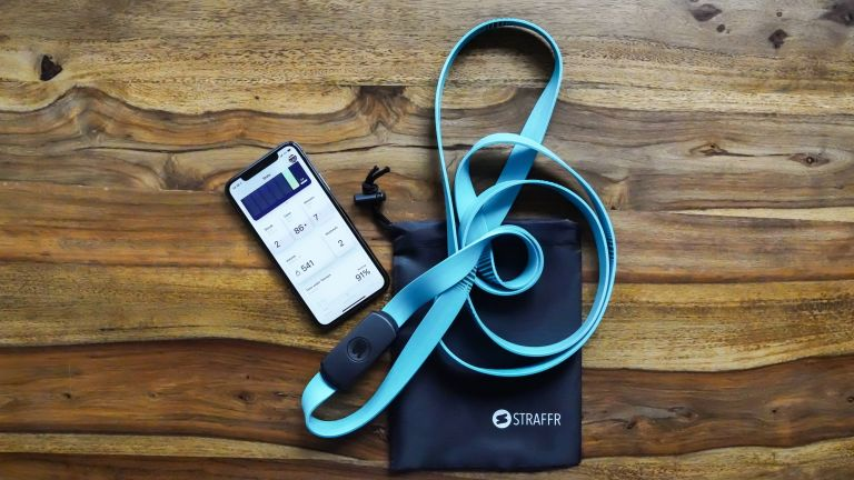 Straffr smart band lies next to a phone connected to the companion app