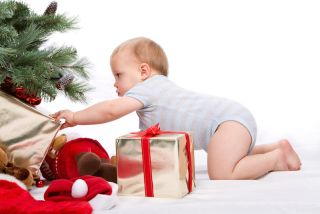 A baby reaches for a present beneath a Christmas tree