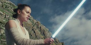 Daisey Ridley as Rey with a lightsaber in Star Wars: The Last Jedi