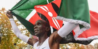Eliud Kipchoge carrying his flag across the finish line