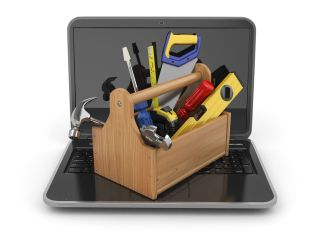 Wooden toolbox with saw, level, screwdriver, hammer and other tools lies atop an open laptop computer.