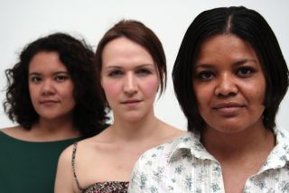 Three women stand together, one looks Hispanic, one looks white, and one looks black.