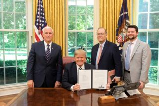 President Donald Trump holds the signed copy of Space Policy Directive 2 in the Oval Office May 24, 2018 with Vice President Mike Pence, National Space Council Executive Secretary Scott Pace and Deputy Executive Secretary and Chief of Staff of the Nationa