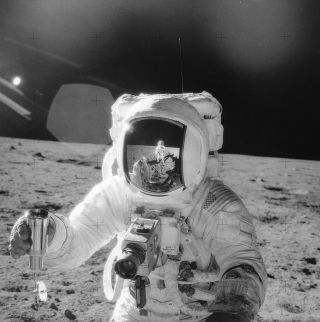 An Apollo 12 astronaut at work collecting a moon rook from the lunar surface.