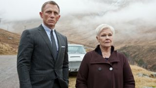 Daniel Craig and Dame Judi Dench stand together in the countryside in Skyfall.