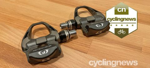 Two Shimano Dura-Ace pedals on a wooden surface, overlaid with a five star badge
