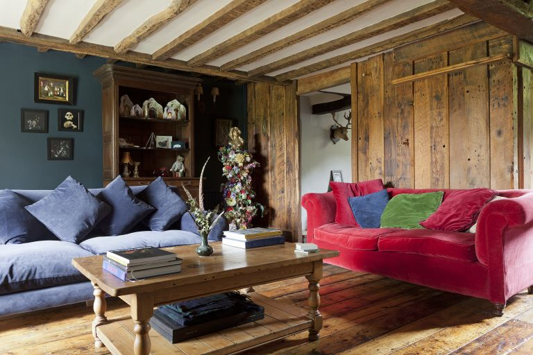 wooden walled living room with beams and red and blue velvet sofas and wooden floors