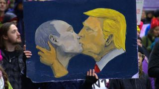 Protest painting of Vladimir Putin kissing Donald Trump
