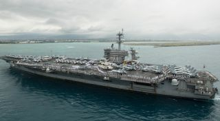 The aircraft carrier USS Theodore Roosevelt, which recently docked at Guam due to an onboard COVID-19 outbreak, is shown here in 2018 as it arrives in Pearl Harbor, Hawaii.