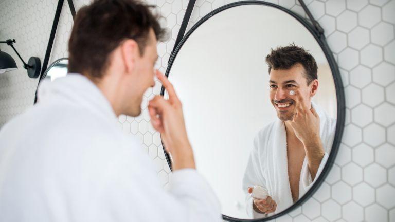 White man looking in the mirror applying a white moisturiser cream under his eyes