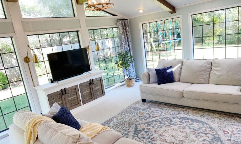 Light living room with crittal-style windows, blue patterned rug, cream fabric couch and wooden TV stand with black accents