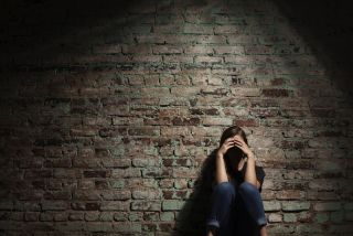 A woman sits alone near a brick wall, her face hidden in shadows.