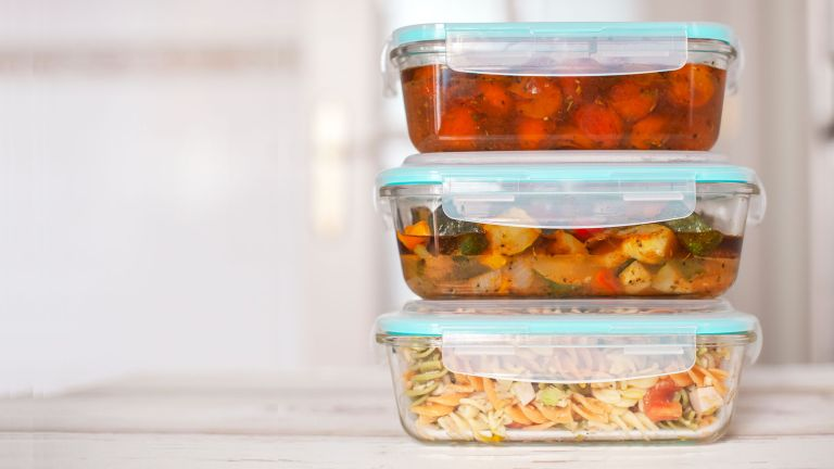 Stack of three tupperware boxes filled with food after a meal prepping session
