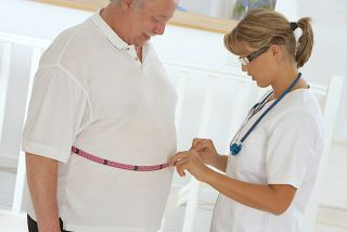A doctor measures the waistline of one of her overweight patients.
