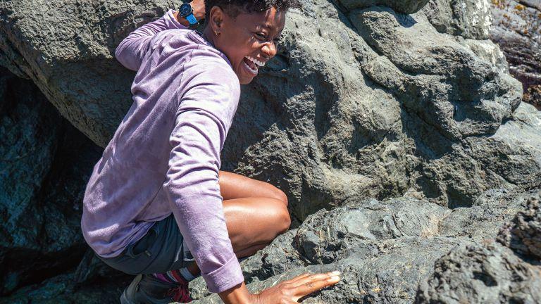 Woman wearing the Smartwool Merino 150 base layer while scrambling over some rocks