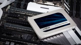 Crucial MX500 SSD laying on top of a motherboard.