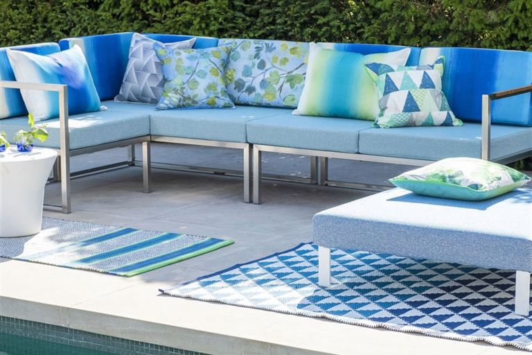 Best outdoor rugs: blue decorative outdoor rugs in garden setting with white and blue outdoor furniture