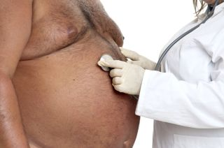 A doctor holds a stethoscope to the chest of an obese patient.