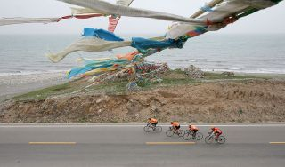 QINGHAI LAKE, CHINA - JULY 18: (CHINA OUT) Cyclists ride bicycles past Prayer Flags during the third stage of the 4th Tour de Qinghai Lake International Cycling Race along Qinghai Lake on July 18, 2005 in Qinghai Province, northwest China. The 4th Tour de Qinghai Lake will last from July 16 - 24, covering 9 stages. Twenty teams from five continents attend this year's race. Tour de Qinghai Lake is held annually since 2002. In 2004, it rose to the top road cycling race in Asia. (Photo by China Photos/Getty Images)