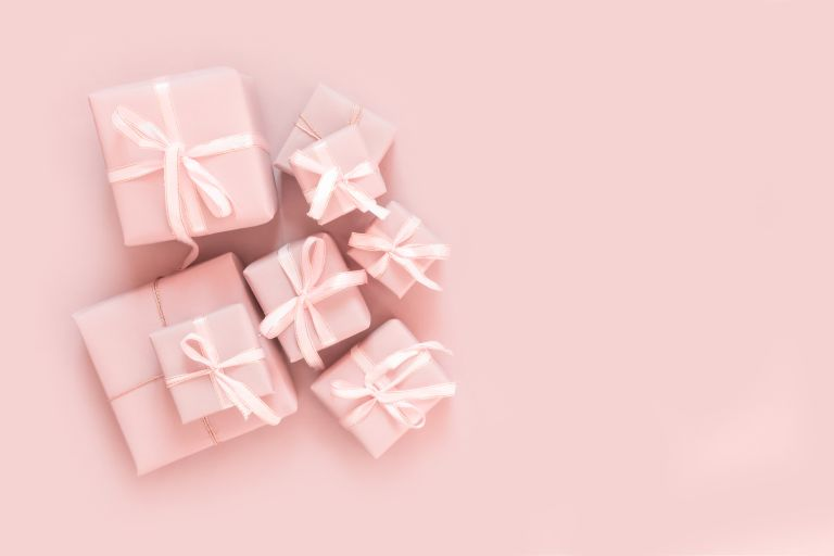 40th birthday gift ideas wrapped in pink paper with pink ribbon.