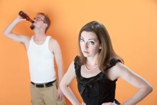 Unhappy Caucasian wife with alcoholic husband on orange background