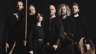 Wardruna posing with a shield and sticks