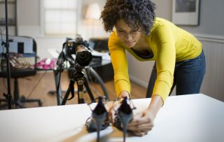 Best camera for product photography: woman photography a pair of shoes with DLR