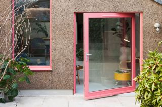 a pivot door in a RAL coral colour
