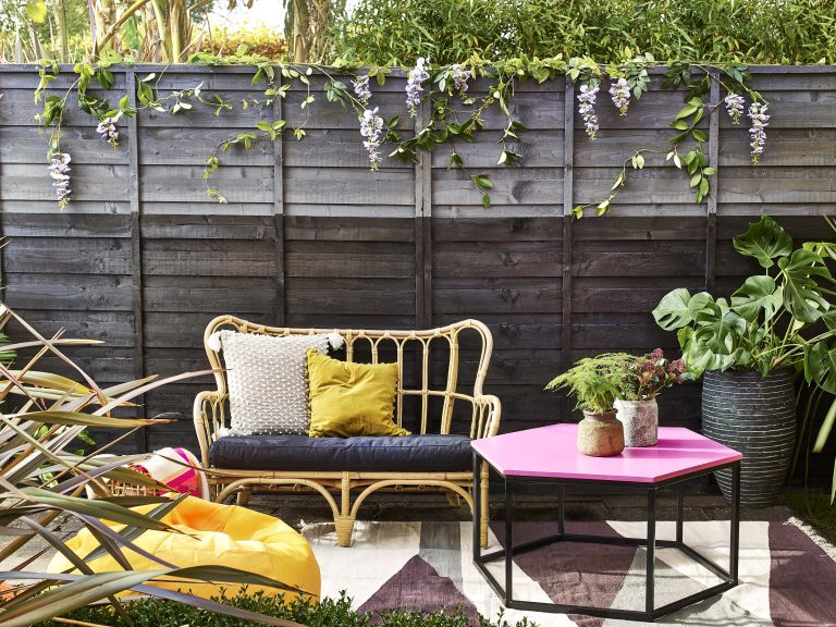 upcycling project showing a painted outdoor table, fence and bench