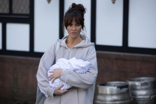 Mercedes McQueen holds Diane's new baby in Hollyoaks.