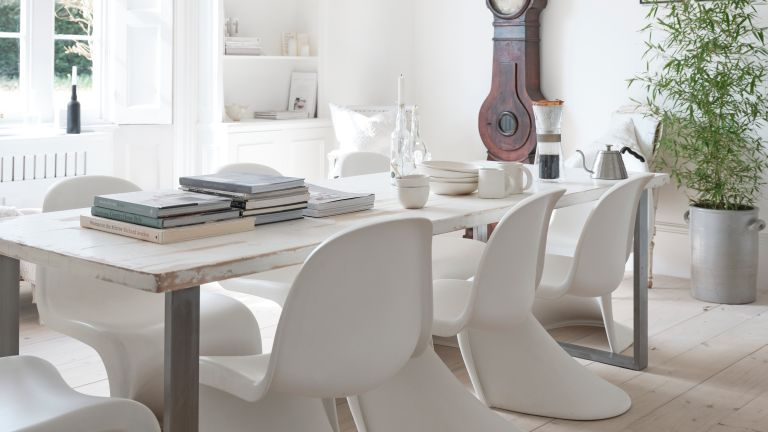 All white dining room with statement chair and vintage clock