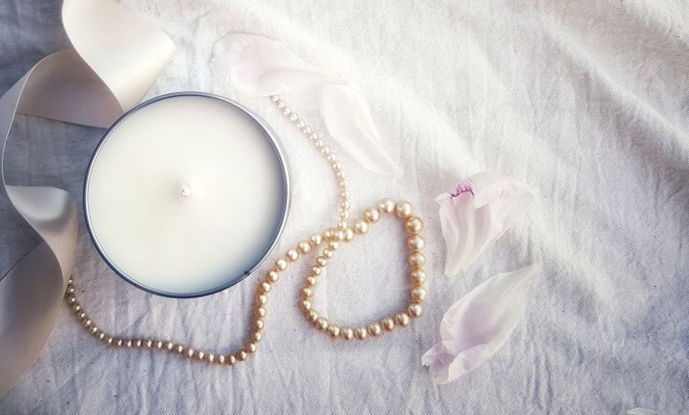 View Of Scented Candle And Pearl Jewelry With Ribbon On White Bed