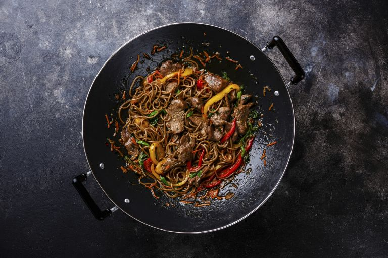Prawn and noodle stir fry in a wok on a grey background