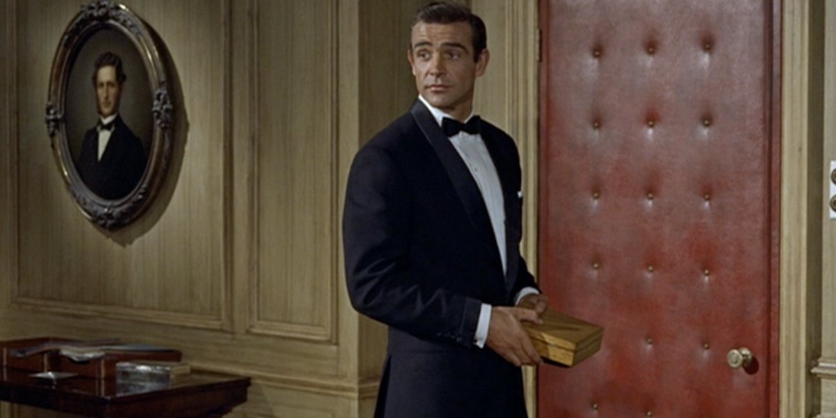 Sean Connery holds a gold box, wearing a tuxedo, in Dr. No