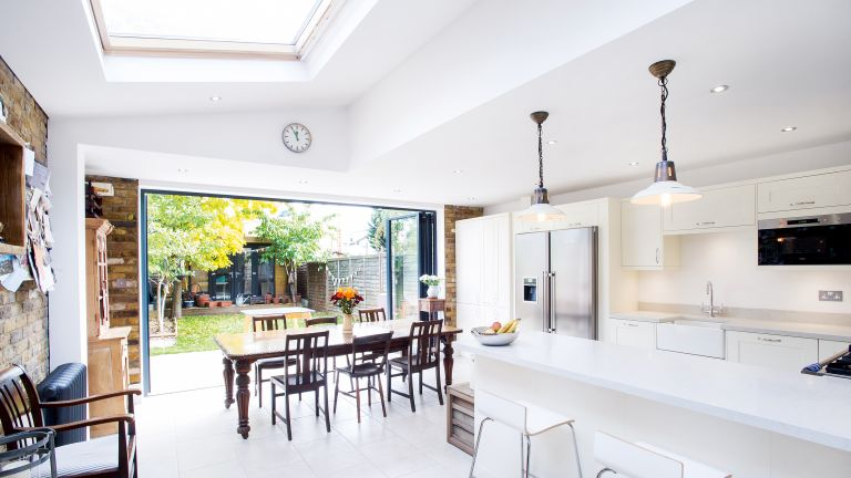 a white and bright kitchen extension opening to the garden