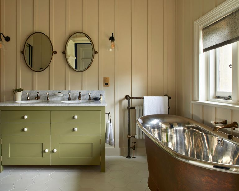 An example of bathroom lighting ideas showing a green double vanity unit below two oval mirrors against a paneled wall