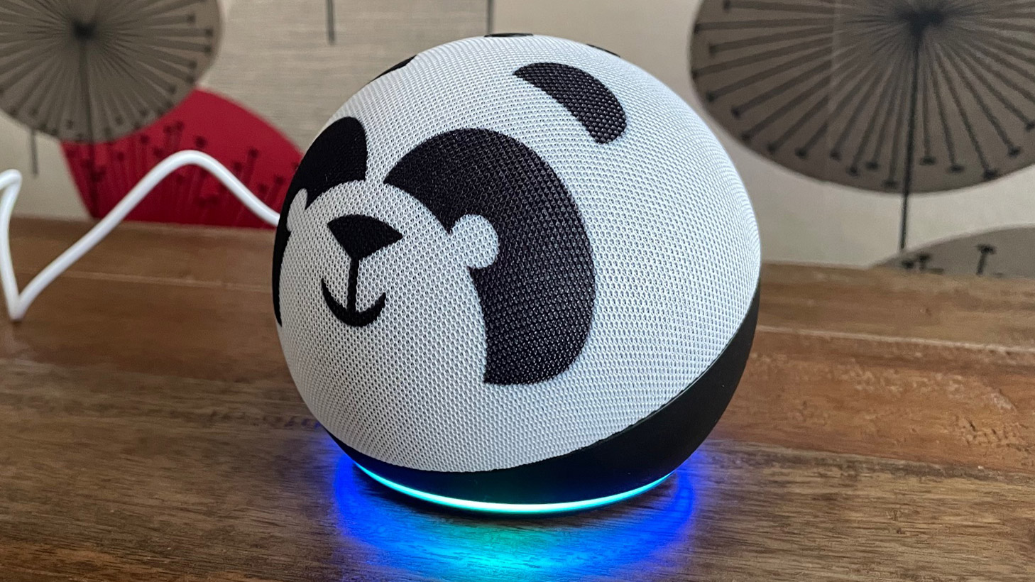 The side view of Amazon Echo Dot Kids smart speaker on a wooden table with a patterned background