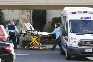 stretcher being wheeled into Life Care Center of Kirkland, Wash., where several cases of COVID-19 have emerged
