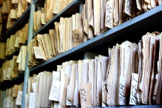 Old paper files in manila folders on shelves in archive.