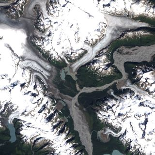 The two glaciers in 1987 were larger and the proglacial lake between them was a lighter blue color.