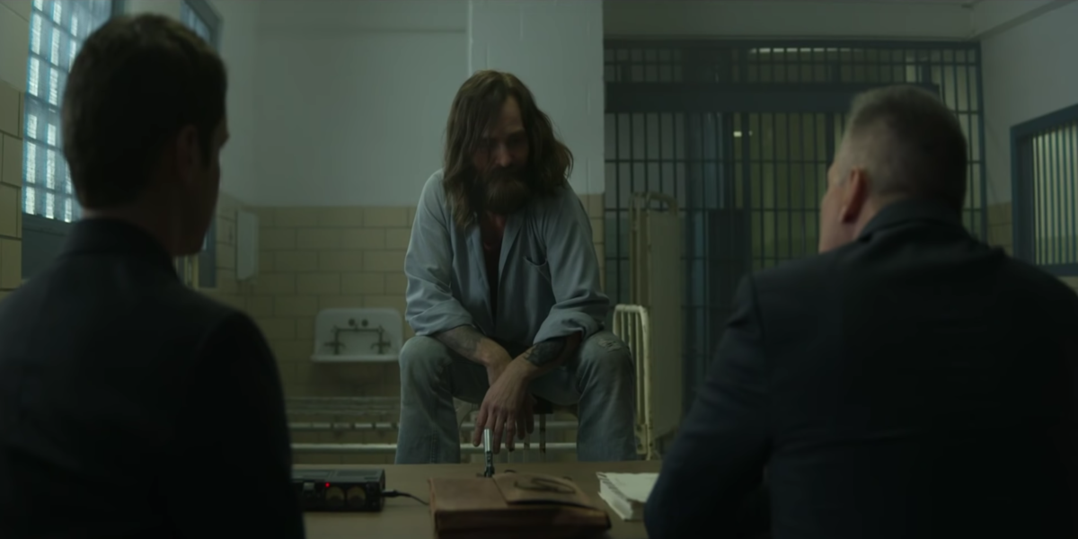 Charles Manson (Damon Herriman) showing a sign of dominance over his interviewers