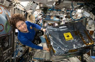 NASA astronaut and Expedition 61 Flight Engineer Christina Koch handles science hardware stowed inside a cargo transfer bag on board the International Space Station in December 2019. Koch is setting a new record for the longest mission by a woman.