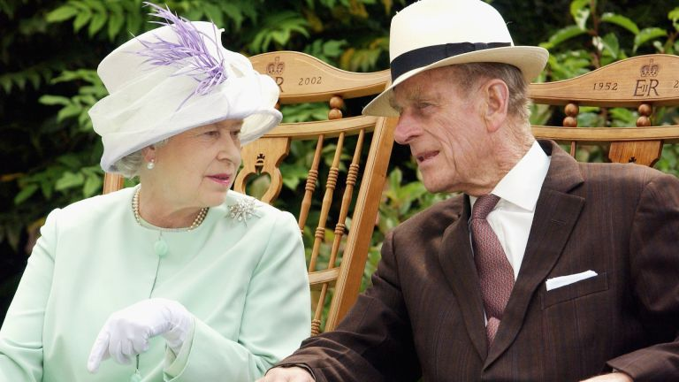 Queen and Prince Philip, the Duke of Edinburgh chat while watching a musical performance in the Abbey Gardens during her Golden Jubilee visit to Suffolk in this July 18, 2002