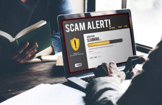"A laptop displaying the warning ""scam alert!"""
