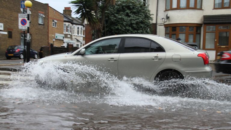 Flooding on a road in East London as a car drives through it following heavy rainfall