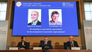 Representatives from the Royal Swedish Academy of Sciences sit in front of a screen displaying the winners of the 2021 Nobel Prize in Chemistry..