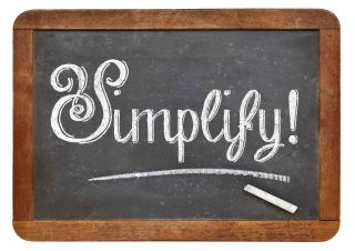 The word Simplify! written in chalk on a blackboard with wooden border