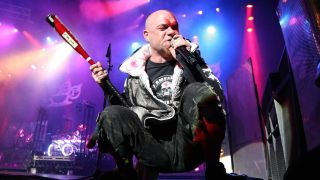 Five Finger Death Punch singer Ivan Moody crouching with a baseball bat on stage