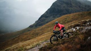 Jenny Tough descends a rocky trail on her loaded mountain bike