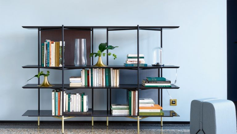 Expert tips on sourcing, large bookshelf with antiques and other treasures in a living room
